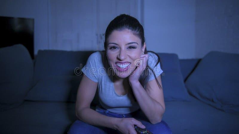 Mujer hispánica hermosa y feliz joven en su 30s que sostiene el telecontrol de la TV que goza en casa de la televisión de observa imagen de archivo