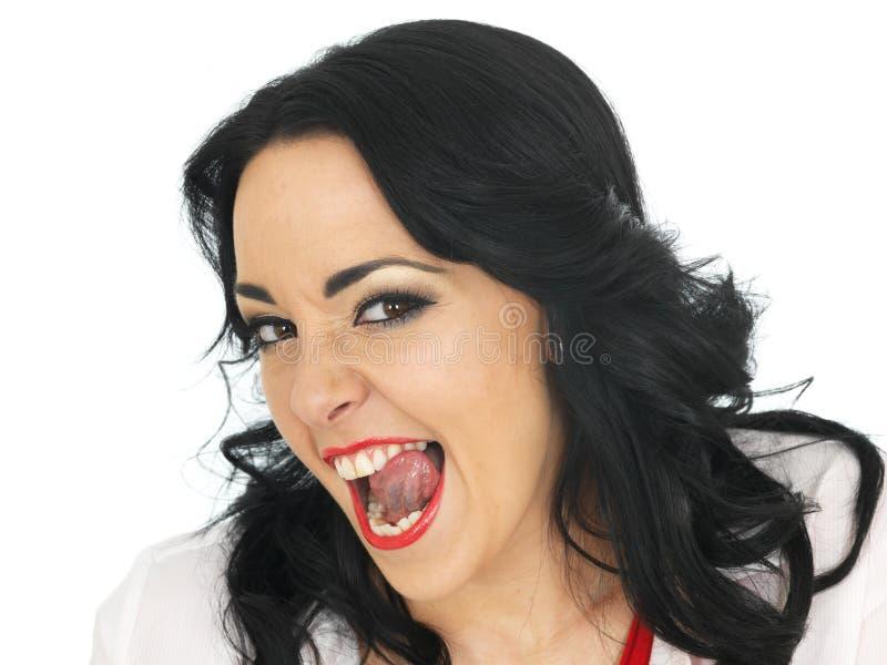 Mujer hispánica joven hermosa fresca que tira de caras tontas y que pega la lengua hacia fuera fotografía de archivo