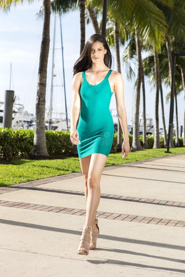 Mujer hispánica joven que camina, al aire libre Puerto deportivo con las palmeras fotos de archivo libres de regalías