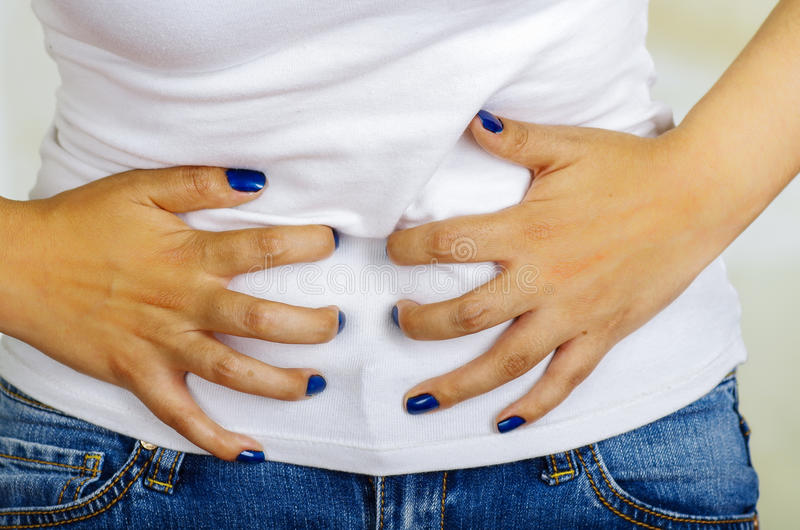 Mujer hispánica joven que toca su vientre, dolor sufridor del período menstrual, concepto femenino de la salud fotografía de archivo libre de regalías