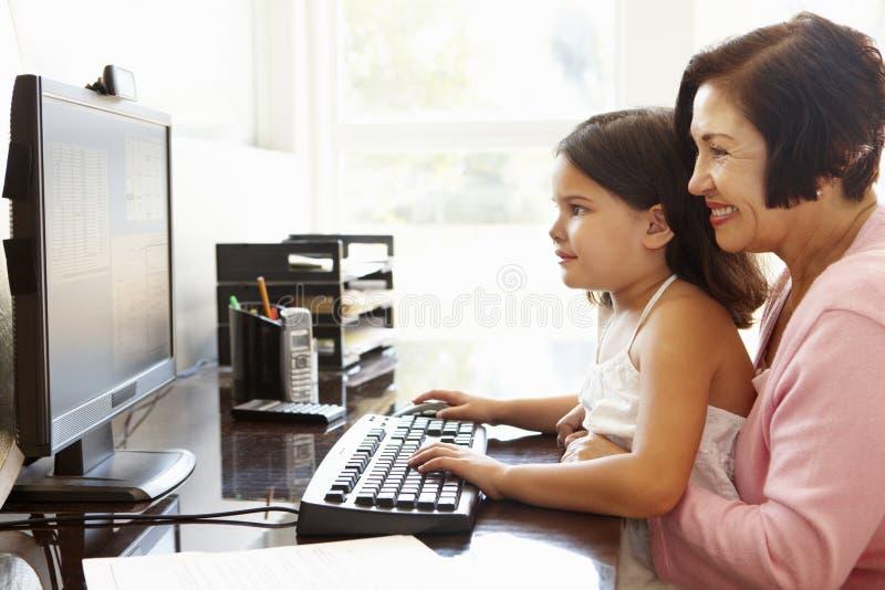 Mujer hispánica mayor con el ordenador y el nieto imagenes de archivo
