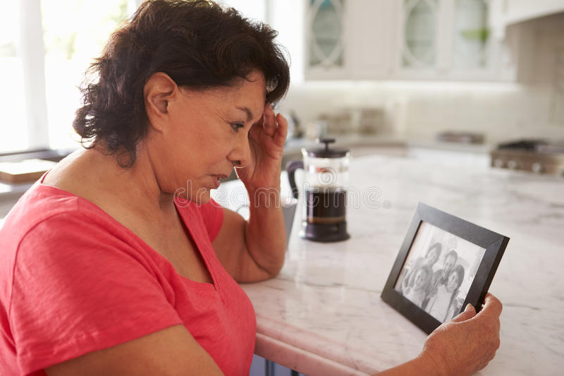 Mujer hispánica mayor en casa que mira la fotografía vieja fotografía de archivo