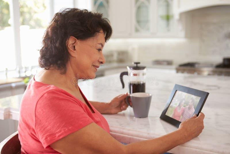 Mujer hispánica mayor en casa que mira la fotografía vieja foto de archivo libre de regalías