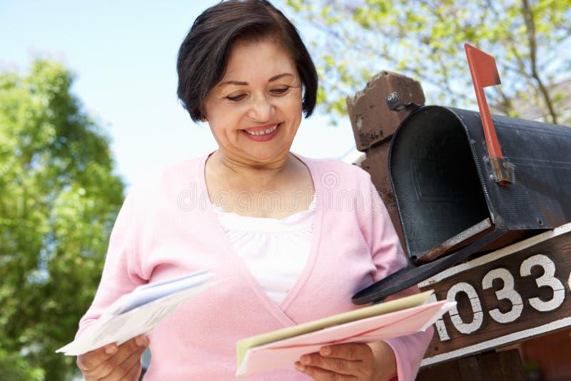 Mujer hispánica mayor que comprueba el buzón imágenes de archivo libres de regalías
