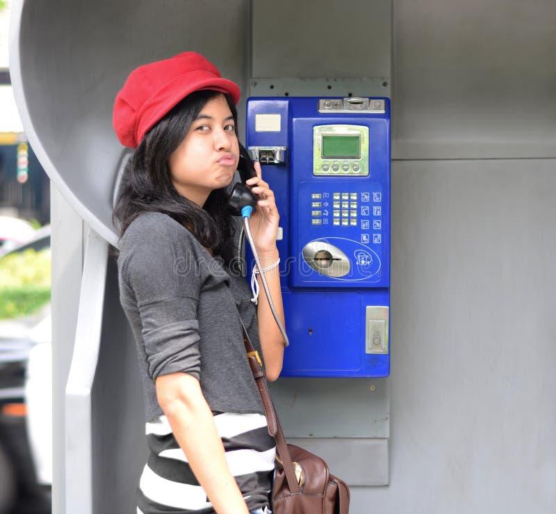 Mujer hispánica que habla en un teléfono público foto de archivo libre de regalías