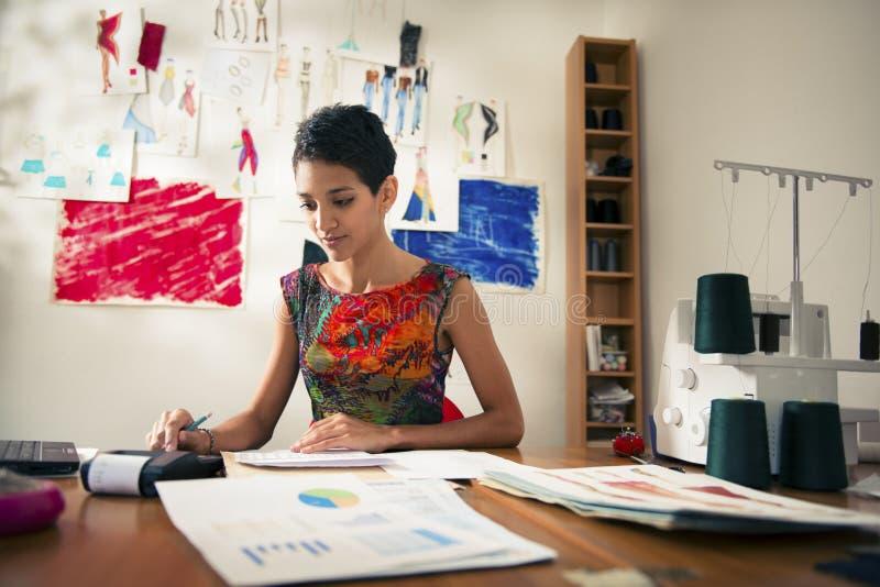 Mujer hispánica que hace el presupuesto en taller de la manera fotografía de archivo libre de regalías