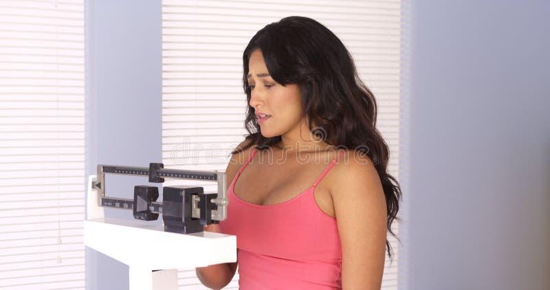 Mujer hispánica triste después de comprobar su peso en escala imagenes de archivo