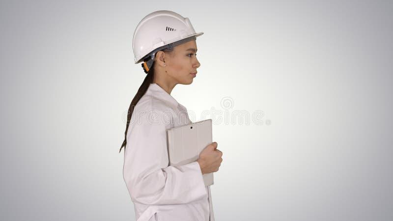 Mujer hisp?nica atractiva en la capa blanca del laboratorio y el casco blanco de la seguridad que camina sosteniendo el cuaderno  foto de archivo libre de regalías