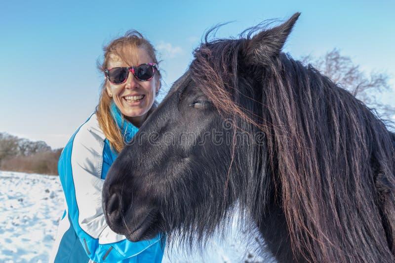 Mujer holandesa del retrato con el caballo del frisian en invierno imagen de archivo