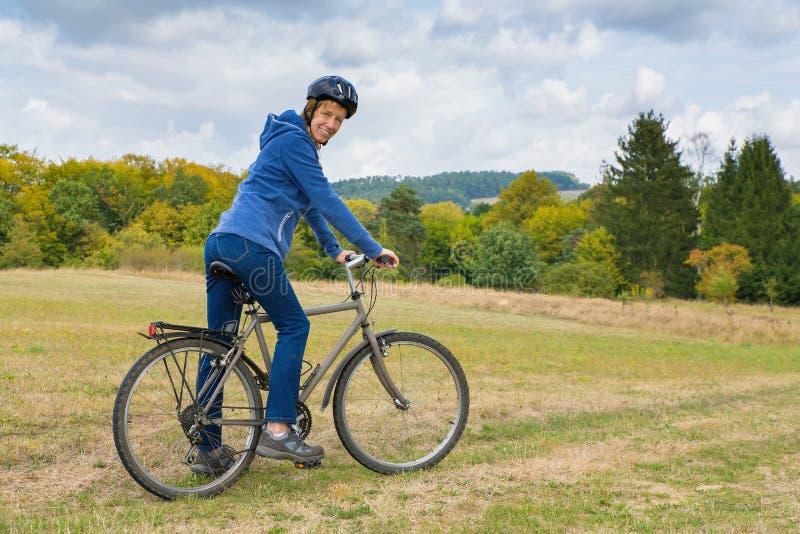 Mujer holandesa en la bici de montaña en naturaleza foto de archivo libre de regalías
