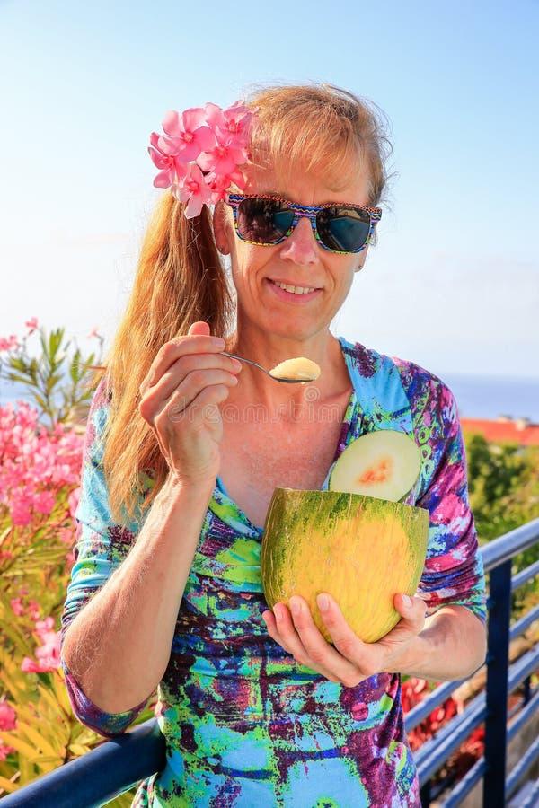 Mujer holandesa que come el melón cerca de adelfa rosado foto de archivo libre de regalías