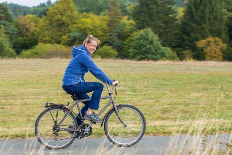 Mujer holandesa que completa un ciclo en la bici de montaña imagen de archivo