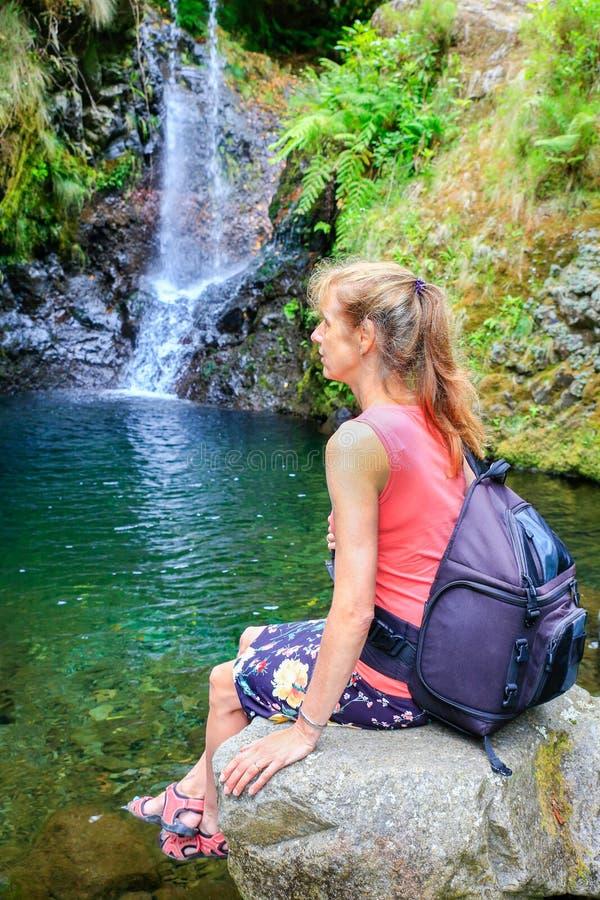 Mujer holandesa que se sienta en roca cerca de la cascada imagen de archivo