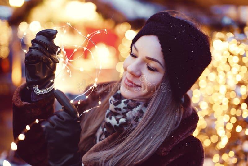 Mujer imaginativa joven que lleva a cabo luces de hadas en mercado de la Navidad imagenes de archivo