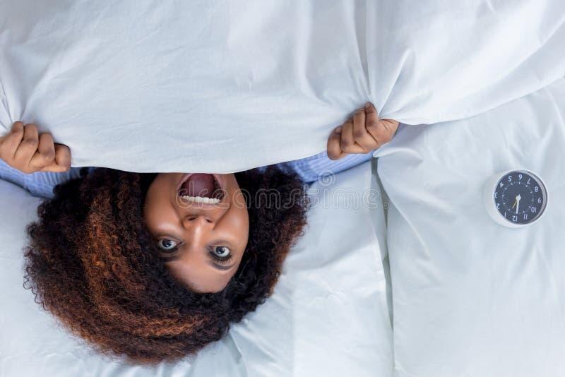 Mujer impresionante africana que grita mientras que miente en la cama imagen de archivo