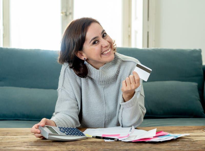 Mujer independiente joven atractiva que parece feliz y emocionada con la tarjeta y finanzas de crédito foto de archivo