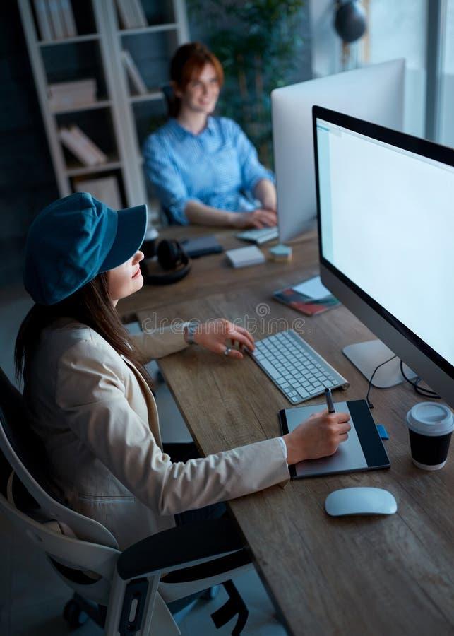 Mujer independiente joven que trabaja en horas extras con la tableta gráfica adentro de fotos de archivo libres de regalías