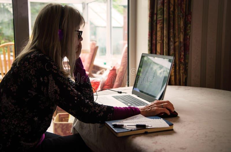 Mujer independiente que escucha webinar en su ordenador portátil, auriculares que llevan fotografía de archivo libre de regalías