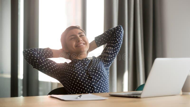 Mujer india feliz relajarse en trabajo de acabado de la silla de la oficina imagen de archivo libre de regalías