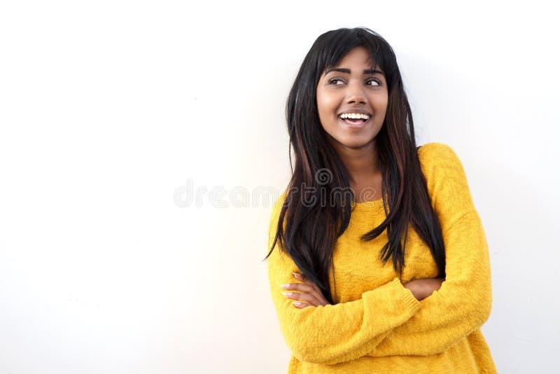 Mujer india joven atractiva que sonríe y que echa un vistazo en el fondo blanco aislado espacio de la copia foto de archivo libre de regalías