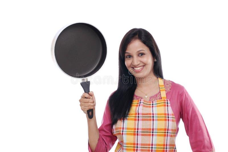 Mujer india joven que sostiene el utensilio de la cocina fotografía de archivo