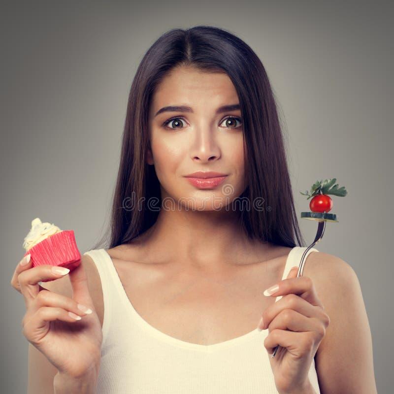 Mujer infeliz con la comida sana y malsana fotos de archivo libres de regalías
