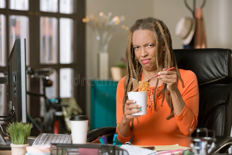 Mujer infeliz con su almuerzo de los tallarines en el trabajo foto de archivo