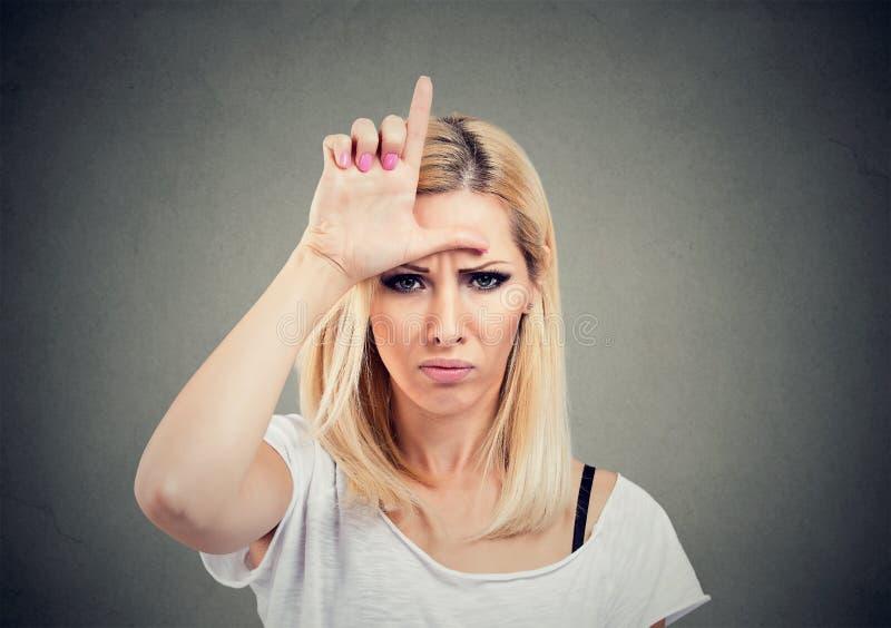 Mujer infeliz del retrato que da la muestra del perdedor en la frente, mirándole con cólera y odio en cara imagen de archivo libre de regalías