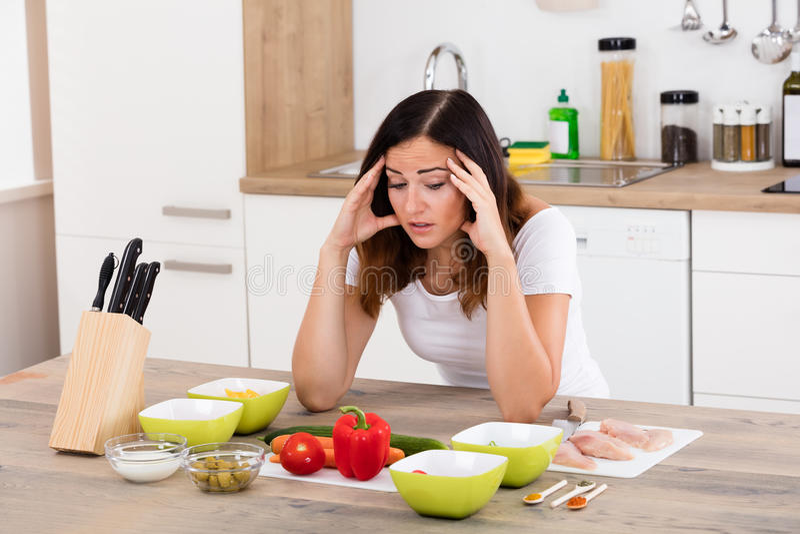 Mujer infeliz en cocina foto de archivo