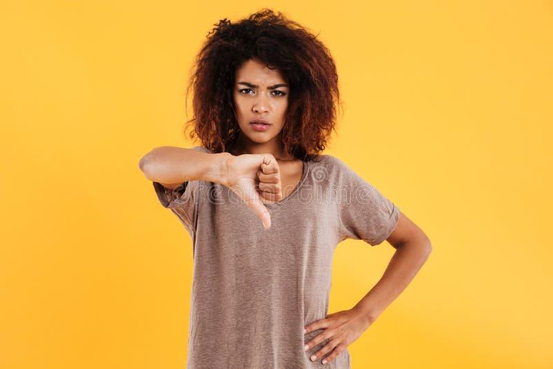 Mujer infeliz enojada joven que muestra el pulgar abajo aislado imagen de archivo libre de regalías