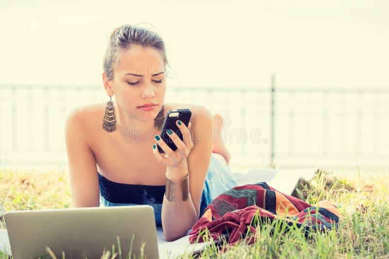 Mujer infeliz escéptica triste que manda un SMS en el teléfono al aire libre en parque imagen de archivo