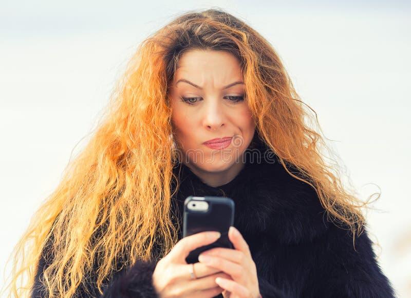Mujer infeliz escéptica triste trastornada que manda un SMS en el teléfono móvil foto de archivo libre de regalías