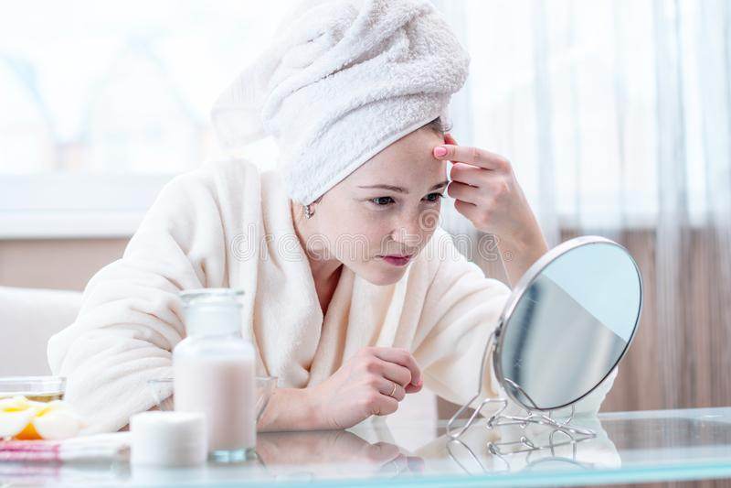 Mujer infeliz hermosa con una toalla en su cabeza que mira su piel en un espejo Concepto de higiene y de cuidado para la piel imagen de archivo libre de regalías