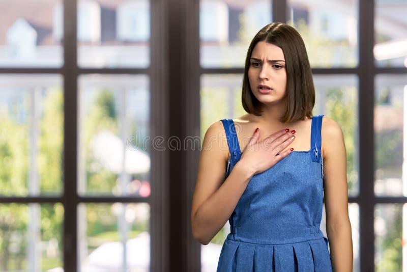 Mujer infeliz joven con la mano en pecho imágenes de archivo libres de regalías