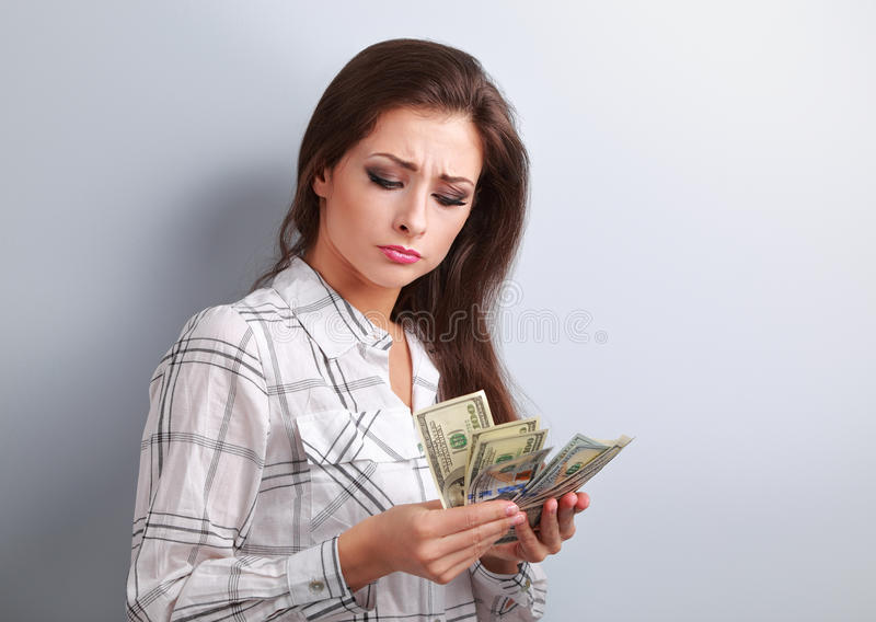 Mujer infeliz joven hermosa que mira en dólares y que piensa ho fotos de archivo