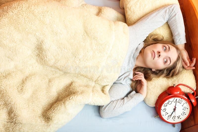 Mujer infeliz que despierta con el despertador imagen de archivo libre de regalías