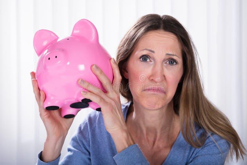 Mujer infeliz que lleva a cabo el piggybank foto de archivo