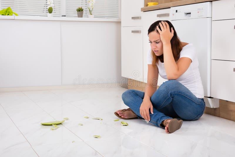 Mujer infeliz que mira la placa quebrada en piso fotografía de archivo libre de regalías