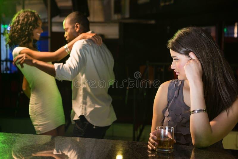 Mujer infeliz que mira un baile de los pares detrás de ella imágenes de archivo libres de regalías