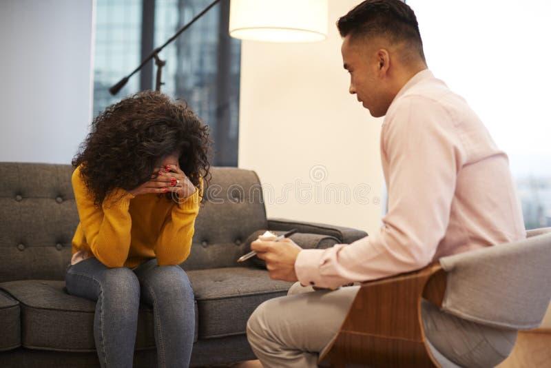 Mujer infeliz que se sienta en la reuni?n del sof? con el consejero de sexo masculino en oficina foto de archivo