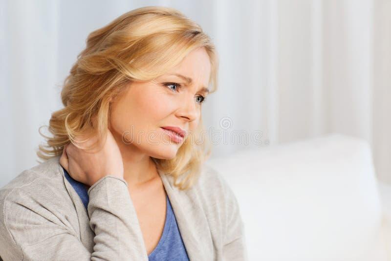 Mujer infeliz que sufre de dolor de cuello en casa imagen de archivo