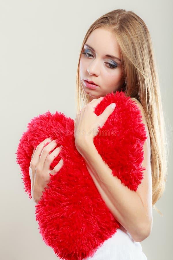 Mujer infeliz triste que sostiene la almohada roja del corazón imagenes de archivo