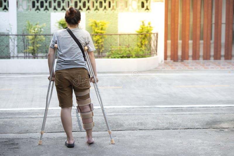 Mujer inhabilitada con las muletas o situaci?n de la ayuda del bast?n o de la rodilla en el lado trasero, cuerpo integral fotografía de archivo