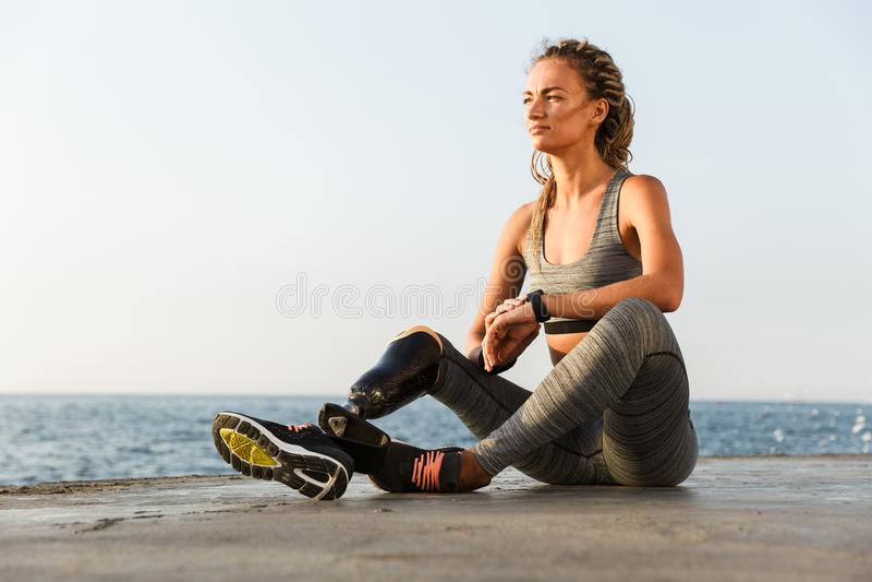 Mujer inhabilitada sonriente del atleta con la pierna prostética fotografía de archivo