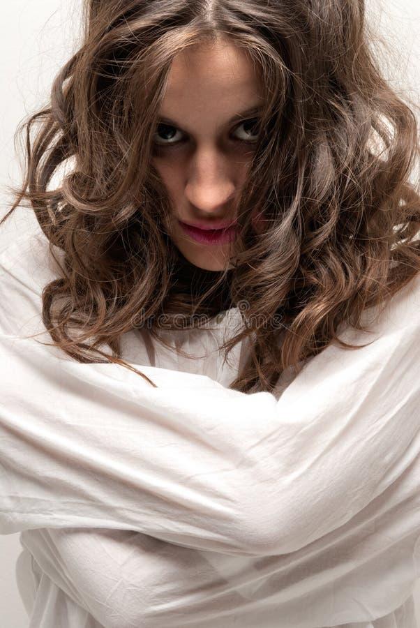 Mujer insana joven con la mirada de la camisa de fuerza fotografía de archivo libre de regalías