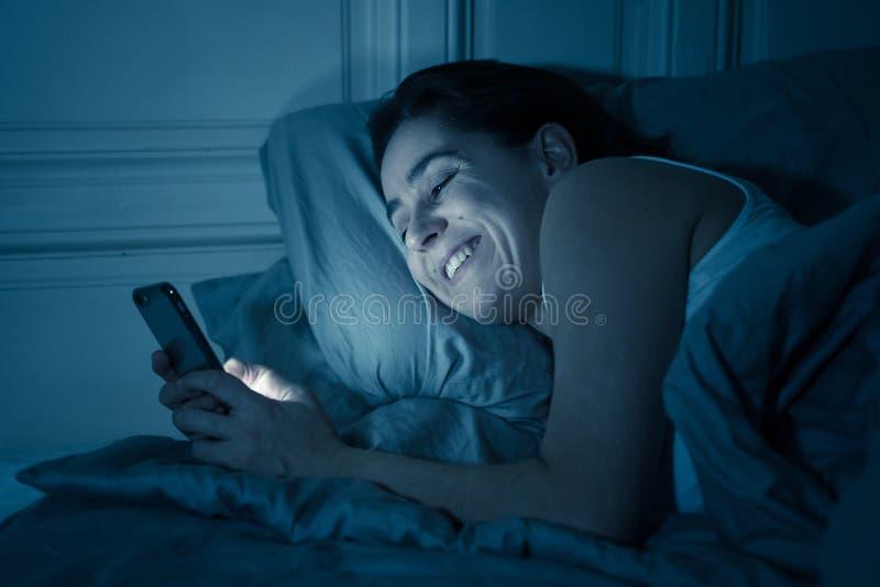 Mujer insomne feliz que miente en cama en Internet usando el teléfono móvil tarde en la noche en dormitorio oscuro fotos de archivo