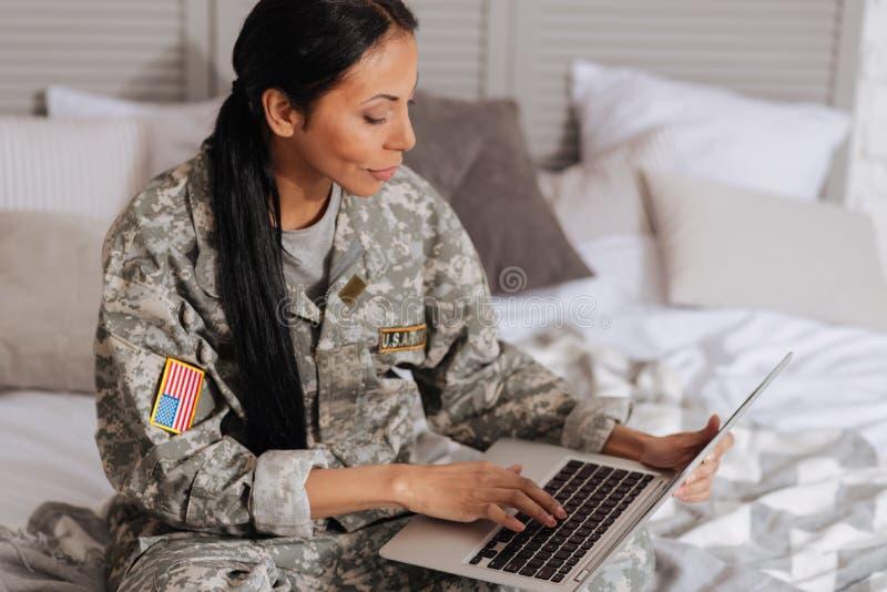 Mujer inspirada enfocada que mecanografía un correo electrónico imagen de archivo