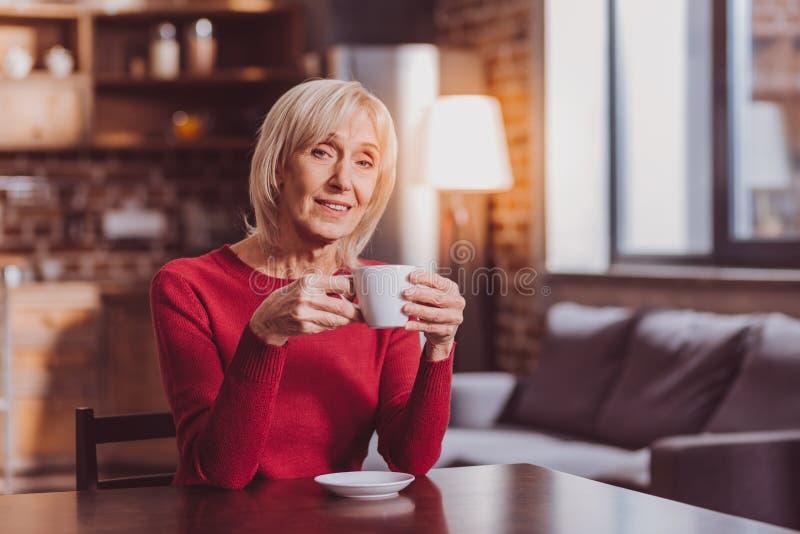 Mujer inspirada que come café y que se relaja fotos de archivo