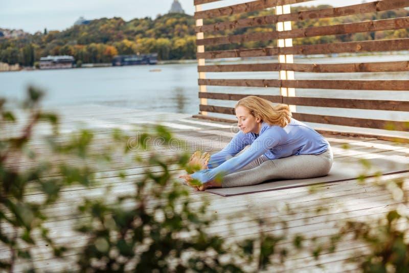 Mujer inspirada que hace estirando ejercicios cerca del agua imágenes de archivo libres de regalías