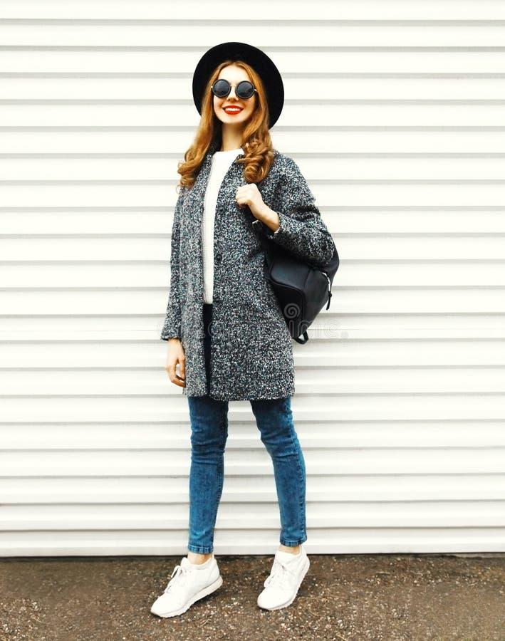Mujer integral de la moda en la capa gris, presentación redonda negra del sombrero imagen de archivo